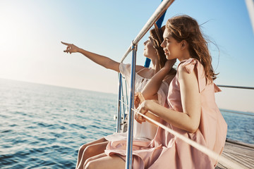 Two attractive european women sitting at bow of yacht, looking at something while pointing at seaside. Friends enjoying being on tropical island, waiting to see dolphins.