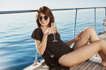 Attractive european brunette in glasses sipping champagne while sitting on floor of yacht in black swimsuit. Rich girl spending leisure on boat her father bought for her.
