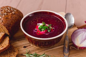 bowl of borscht with pieces of bread and onions on a wooden table