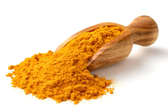 Turmeric powder in the wooden scoop, isolated on white