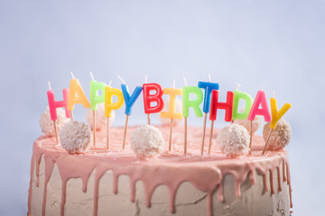 pink white cake with coconut balls and happy birthday candles