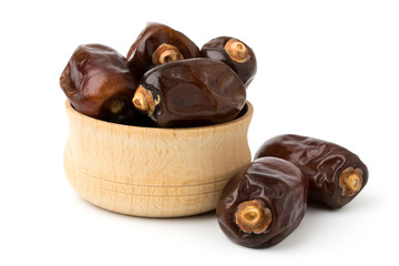 Dried dates in a wooden bowl on a white. Wall mural