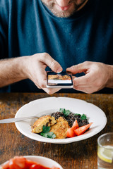 Man takes pictures of vegetarian food that he eats (black quinoa and cutlets from oatmeal and prunes). Healthy vegetarian food concept