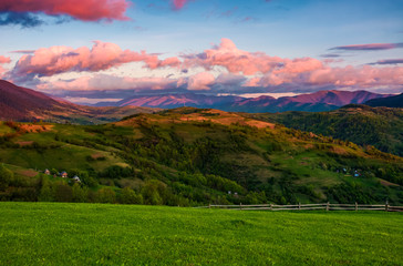 beautiful rural area in mountains. gorgeous landscape with beautiful cloud formations over the mountain ridge in red light at sunset