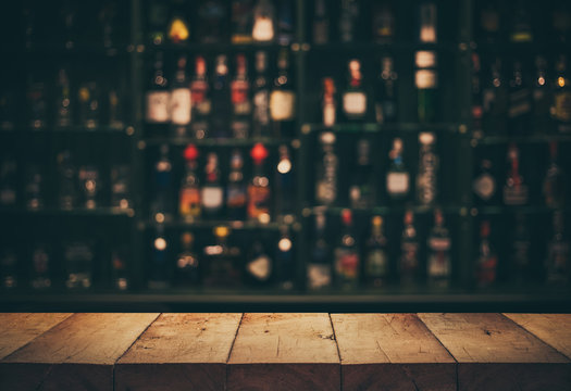 Empty the top of wooden table with blurred counter bar and bottles Background