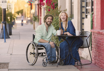 Woman with Man in Wheelchair at Cafe Table