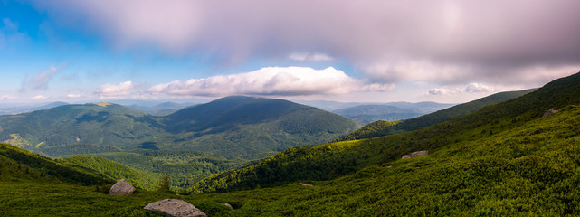 panorama of beautiful mountain landscape. beautiful scenery with clouds coming over the hills