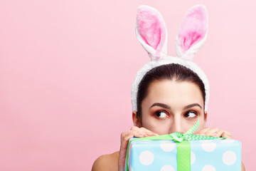 Happy young woman wearing bunny ears and holding present