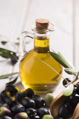 Olives and a bottle of olive oil on white dark wooden table