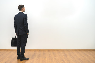 The man with a case standing on the white wall background