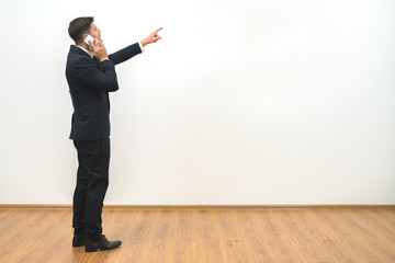 The businessman phones and gestures on the white wall background