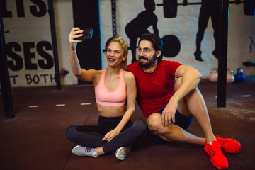Young couple taking a selfie in gym.