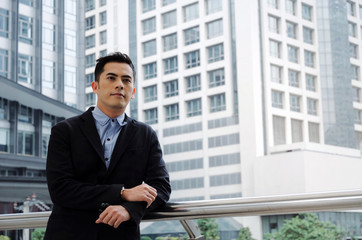 young handsome asian business man wearing modern black suit standing looking into camera in building city background, confident, team leader, successful, manager, portrait and entrepreneurship concept