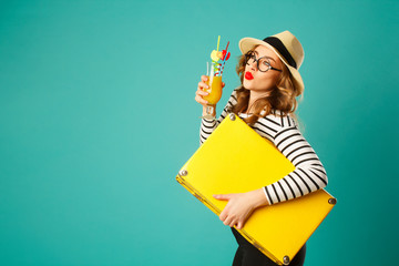 Portrait of young beautiful blond woman in hat with yellow big suitcase holding cocktail over blue background