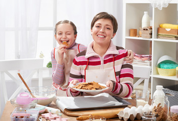 Mother and daughter baking cookies, girl eat cookie, home kitchen interior, healthy food concept