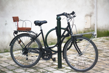 Black bicycle with an homemade comfy child seat, parked in a paved street, Orléans, France, winter 2018