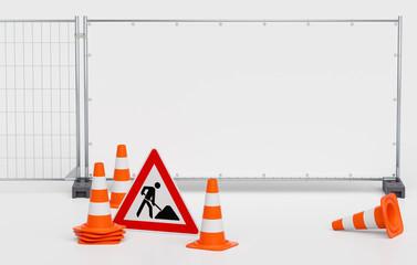 Gruppe von Pylone Pylonen Verkehrshütchen Leitkegeln mit Baustellenschild vor Mobilzaun Bauzaun mit weißem unbedruckten Banner