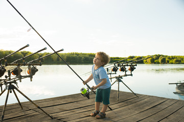 Angling child with fishing rod on wooden pier