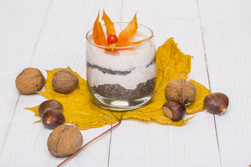 Cream with flower in glass on maple leaf with nuts