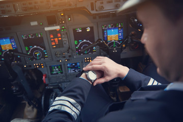 Close up male pilot looking at watch while flying plane in cockpit. Job and clock concept