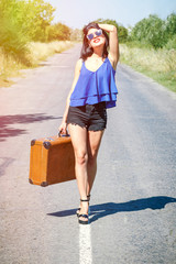 Happy Brunette beautiful girl traveler with suitcase on road, hitchhiking. Concept of travel, adventure, vacation, freedom. Waiting for car or bus