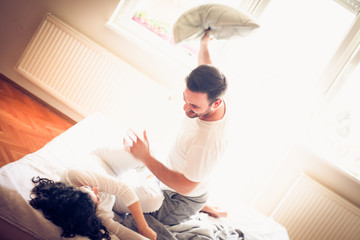 Pillow fight between couple.
