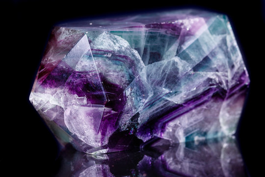 Macro mineral stone Fluorite crystal on a black background