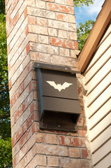 Bat House on a Brick Chimney Outside in Summer.