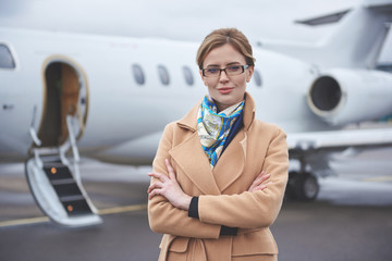 Portrait of smiling businesswoman looking at camera while standing at airfield. Career concept