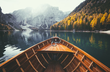 Wooden rowing boat on a lake in the Dolomites in fall Wall mural