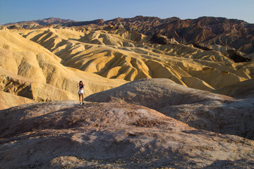 Girl in the landscape, amazing view of mountains ridges on sunny day, attractive young lady is standing on the hill, extreme heat and drought at Zabriskie Point, Death Valley National Park, California