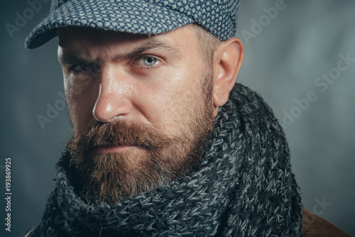 eaa4c8ebe7e Closeup portrait stylish bearded man on gray background. Autumn-winter  fashion. Attractive man with beard and moustache wearing gray cap and scarf.
