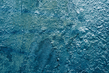 The wall is painted blue with shiny paint on an old paint