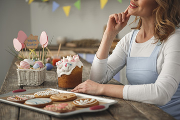 Laughing woman sitting in the cuisine. Ready holiday pastry standing in front of her