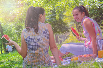 Two young women enjoying  conversation and eating watermelon on picnic outdoors