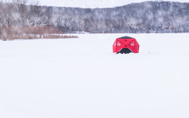 A red fishing cabin in a snowy lake