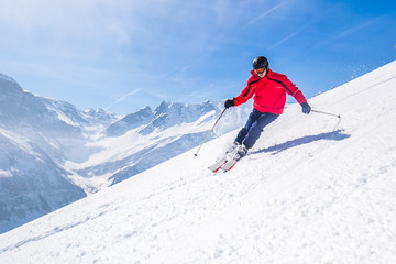 Man skiing on the prepared slope with fresh new powder snow in Swiss Alps, Lenzerheide, Switzerland