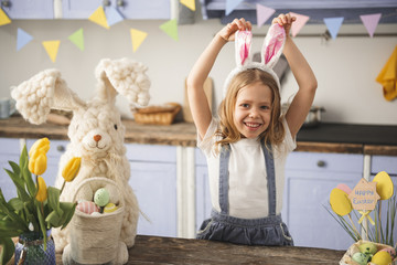 Waist up portrait of smiling kid posing in the kitchen with rabbit ears on head. Colored eggs and toy bunny standing on the table