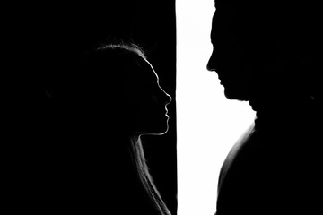 Silhouette of a guy and a girl. A girl stands on a black background and a guy stands on a white background. Black and white photo