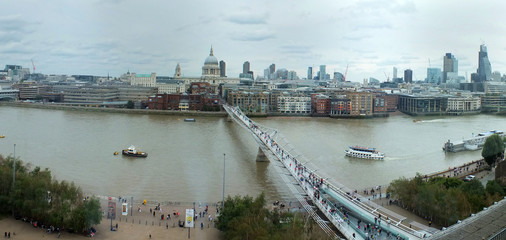 wide panoramic aerial view of the city of london with historic landmarks and building in the business district with pedestrian bridge crossing the river thames