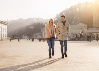Look. Full length of happy young lovers are spending time outdoors while having cheerful mood. They are walking on square while girl in sunglasses is pointing finger on something down. Copy space