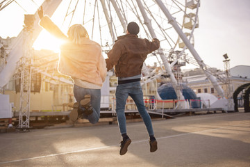 Full of energy. Full length back view of young girlfriend and boyfriend are jumping on street while holding hands. Sunset light and ferris wheel on background