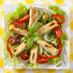 Chicken salad on the plate. Grilled chicken meat with tasty selection of vegetables.