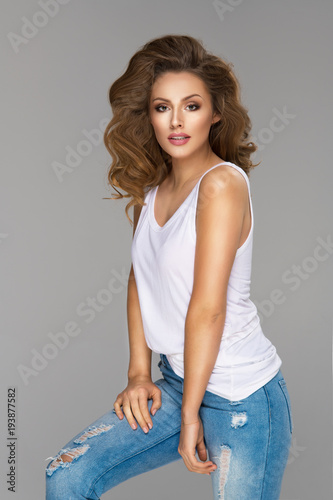 6fb54e77f89 Young beautiful woman wearin white top and jeans on grey background ...