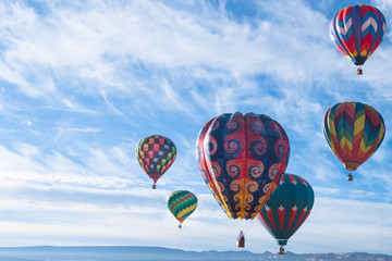 Colorful hot air balloons flying over the mountain.  New maxico, USA.