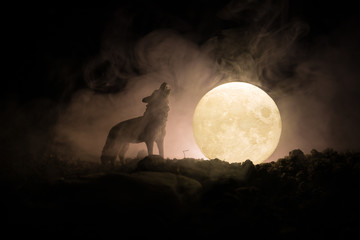 Foto auf Leinwand Wolf Silhouette of howling wolf against dark toned foggy background and full moon or Wolf in silhouette howling to the full moon. Halloween horror concept.