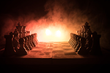Chess board game concept of business ideas and competition and strategy ideas concep. Chess figures on a dark background with smoke and fog. Business leadership and confidence concept.