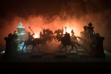 Medieval battle scene with cavalry and infantry on chessboard. Chess board game concept of business ideas and competition and strategy ideas Chess figures on a dark background. Selective focus