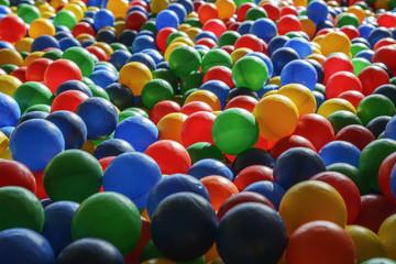 Background texture of multi-colored plastic balls on the playground.