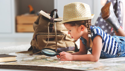 funny child girl tourist with world map, backpack and magnifier.